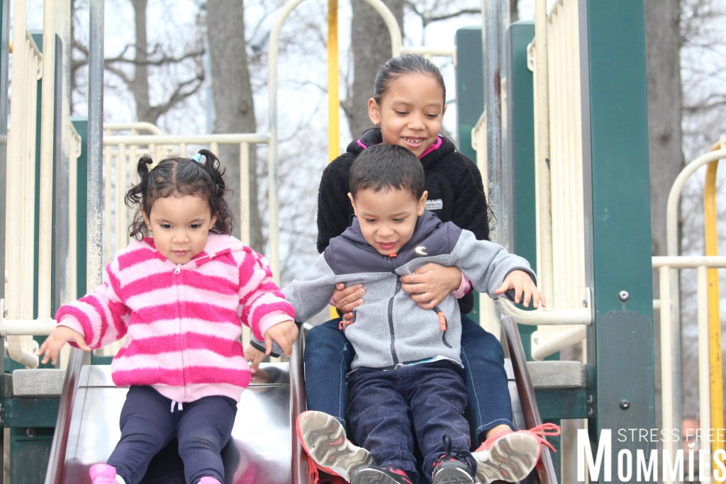 brother and sisters playing on the slide